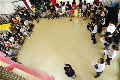 """昨日,在""""教员临时殴打孩童""""确当事幼儿园内,朝阳区教委、园方和警梗直向孩子家长们说明状况。摄影/新京报记者 尹亚飞"""