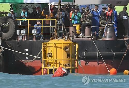 资料图片:救援队正在向海里下放潜水钟。韩联社