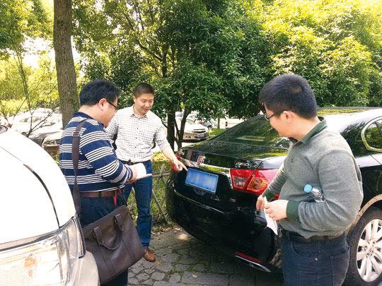 图为5月2日浙江省杭州市纪委检查组工作人员在西溪湿地景区停车场检查公车私用情况。记者 杨诗琪 摄