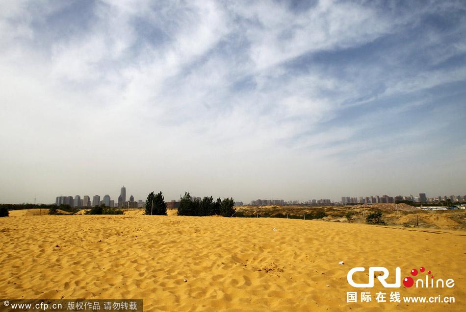 郑州市北三环与九如路交叉口西南角,有一处高约十米的大沙堆,面积约有四个蓝球场那么大。置身其中,如同到了沙漠一般。远处就是郑州的CBD。