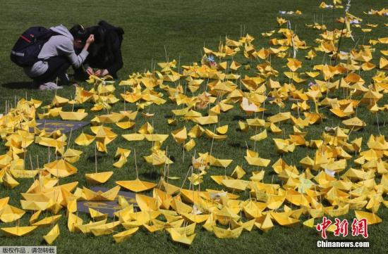 """当地时间5月6日,韩国首尔,韩国佛诞日假期的最后一天,民众在首尔广场用黄色的纸张折成纸船,并摆放成爱心的模样,以追思、悼念""""岁月""""号客轮沉没事件的遇难者。"""