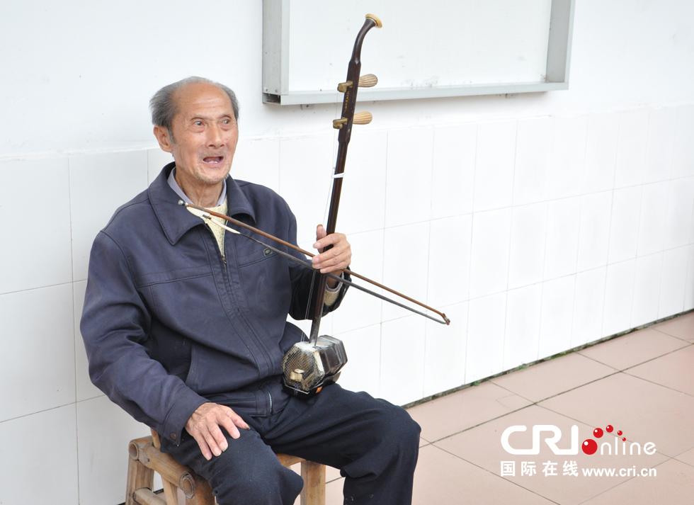 80岁的黄石文老人喜欢坐在门前拉二胡