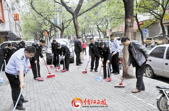 近日,河南信阳市行政执法支队在胜利南路开展卫生大扫除。