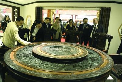 中国红木馆内,一款标价280万元、名为《山水》的红木圆桌吸引了顾客围观。