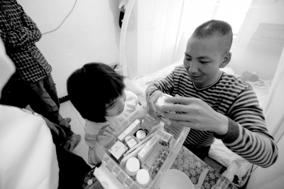小颖和爸爸在医院附近的出租屋内给哥哥整理治疗所需的药品。京华时报记者陶冉摄/视频
