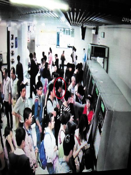 长沙地铁监控系统捕捉到扒窃嫌疑人(打红圈者)正在行窃的瞬间。 均为 颜家文 翻拍