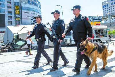 民警持枪配犬巡逻。京华时报记者蒲东峰摄