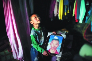 王光荣唯一的儿子手捧父亲遗像。早报记者 杨一 图