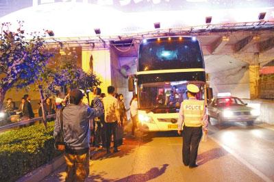 """公交车乘客登上大巴车为其""""增重""""-大巴车卡在涵洞 公交乘客压低车高清图片"""