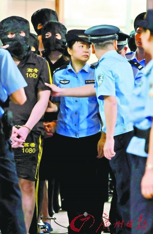 10名被告人戴着头套,被带进法庭。 记者黎旭阳 摄