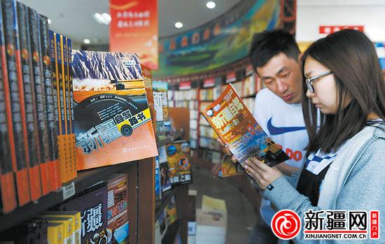 新疆网讯 5月21日,在南门新华书店,新婚夫妇王嘉玉(右)和马俊杰在挑选新疆自驾游书籍,他们计划本月底自驾出游。