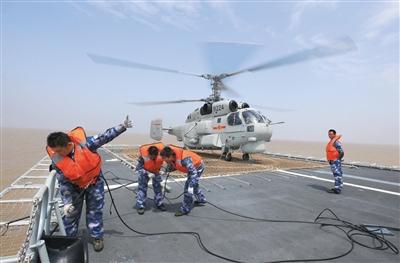 22日,航空兵地勤人员在郑州舰上准备直升机冲洗车。新华社发