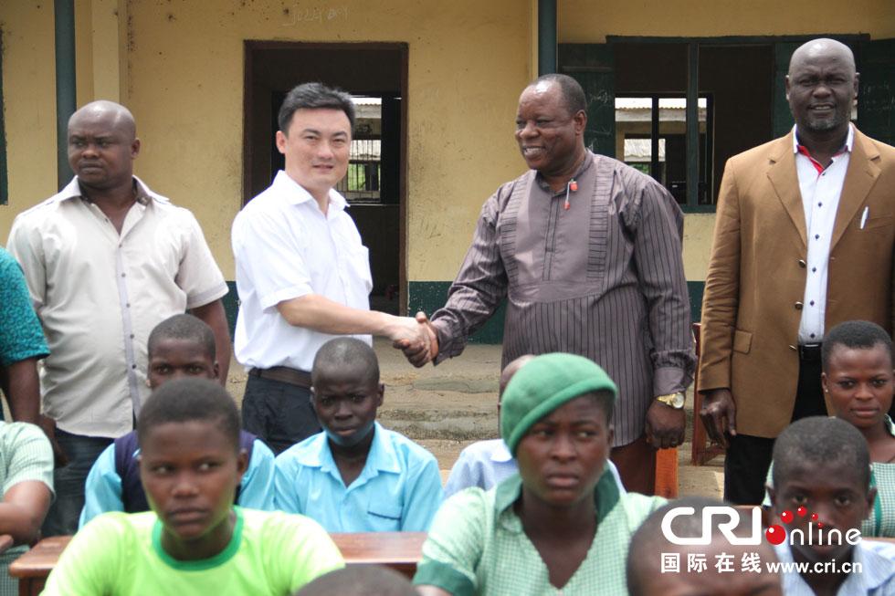 伊故鲁塔社区中学学生围坐在葛洲坝尼日利亚公司捐赠的课桌椅旁 摄影: 张威伟