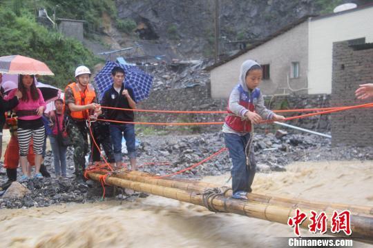 贵州省铜仁市江口县因强降雨,致道路溢水中断,商铺、民房被淹受损。图为地势低洼处四溢的洪水犹如河坝泄洪。 田维虎 摄