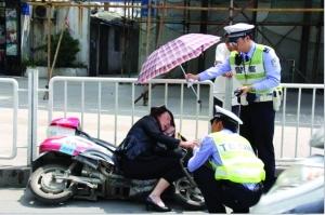 交警为中暑的女子撑伞网友供图