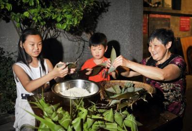 婆婆手把手教孙儿包粽子。