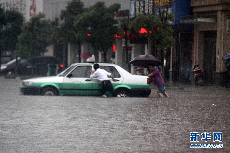 6月1日,在江西省瑞昌市赤乌中路一店铺门口,一辆电瓶车浸泡在积水中。