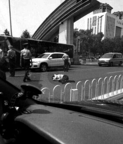 被撞伤的交警倒在地上。央视截图