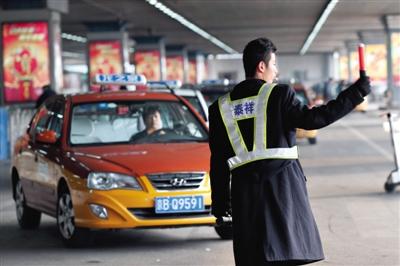 2月17日,首都机场第二航站楼出租车候车区,调度员正在指挥上客。新京报记者 尹亚飞 摄