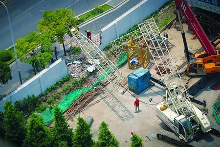 昨日,倒塌的塔吊压垮了围墙,并悬在道路上方。 /晨报记者 肖允