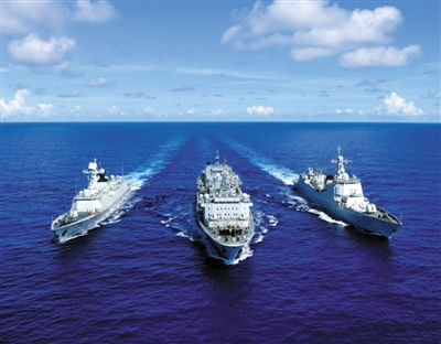 """6月13日上午,在西太平洋海域,海军赴美参加""""环太平洋-2014""""演习舰艇编队综合补给舰千岛湖舰(中)与海口舰(右)和岳阳舰实施海上补给。新华社发"""