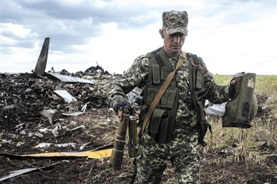14日,乌克兰东部卢甘斯克机场附近,一名武装人员从被击落的伊尔-76运输机残骸中拣出武器碎片。新华社发