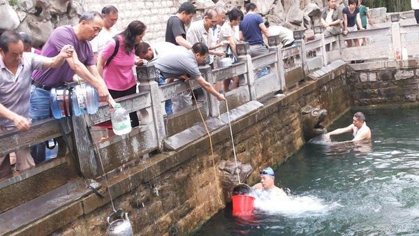 济南黑虎泉景区内,市民在出水口打水,不少游泳爱好者泡在水中。