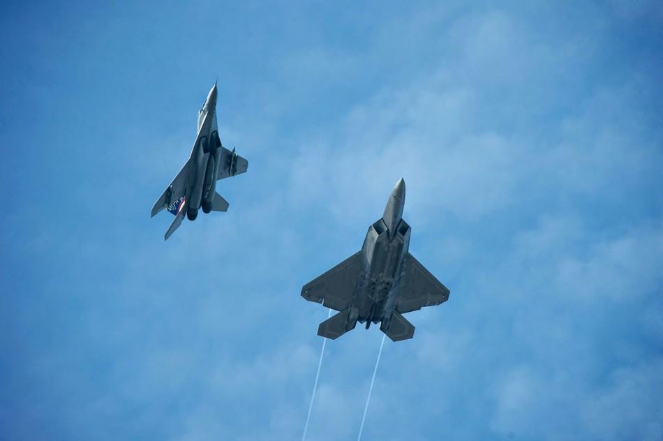 美国空军f-22与f-15战机在空中格斗画面,可以看到f-22战斗机在释放图片