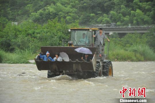 图为:被困的3名村民被铲车营救。 任益 摄