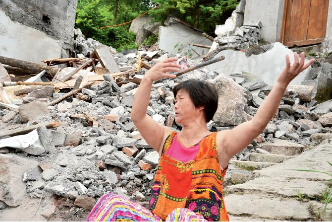 """52岁的冯建平始终固执地认为,自家违章建筑被强拆与她反对""""村长卖地""""有关。陈瑜 摄"""