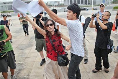 21日狗肉节当天,动物保护人士杜玉凤在玉林市政府广场声称要见市长,不明人士把她打算写标语的纸张没收。