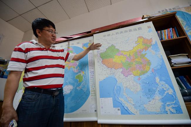 6月23日,湖南地图出版社总编辑雷宜逊在介绍竖版《中华人民共和国地图》。新华社记者白禹摄