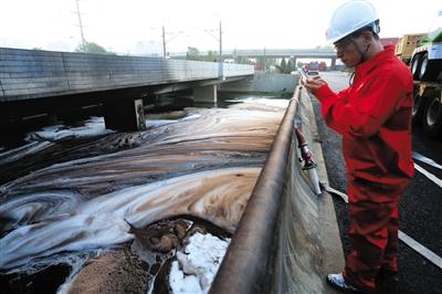 昨日,一名消防人员拍摄市政污水管网排入鞍子河的原油情况。新华社发