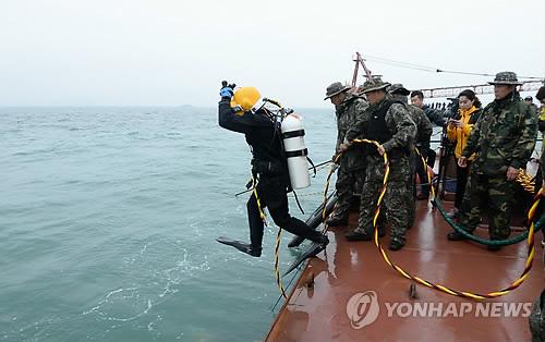 资料图:5月14日,韩国潜水员准备跳进海里开展搜救工作。