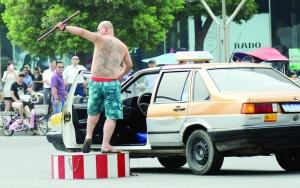 的哥戴着墨镜,光着膀子,叼着香烟,挥舞棍棒指挥交通 通讯员 车佳 摄