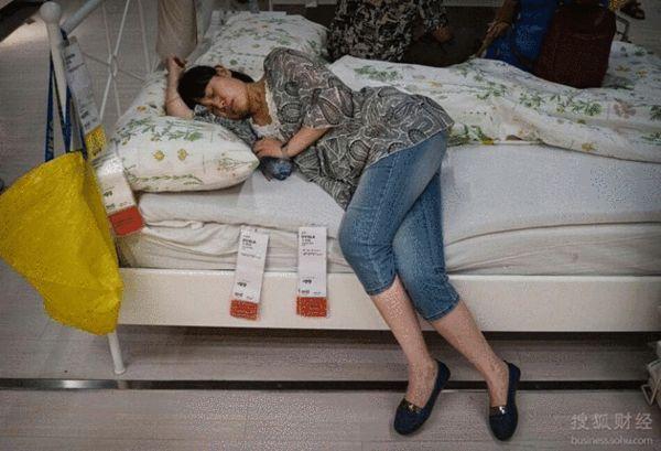 图为顾客在宜家商场陈列的沙发或床上睡觉休息.