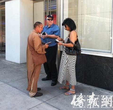 一名假和尚在向路人乞讨。