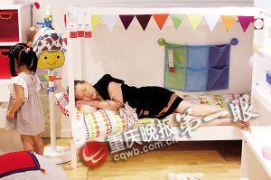 一位婆婆躺在儿童床上,想睡但又怕影响其他顾客购物。