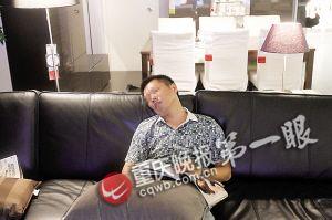 一名男子坐在选购的沙发上睡着了