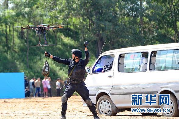 7月14日,在反恐演练现场,一名特警将现场搜到的证物挂在警用无人机上运离现场。当日,吉林省反恐维稳实战演练汇报会在长春举行。 新华社记者 张楠