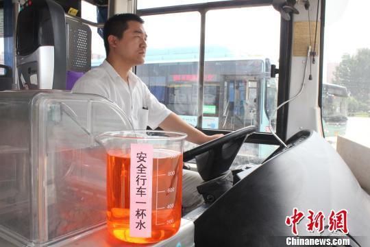 图为公交司机携带盛满水的量杯稳当行驶。 马义恒 摄