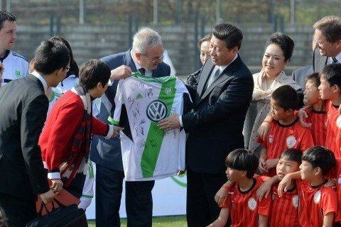 2014年3月29日,柏林奥林匹亚体育场足球场,习近平和夫人彭丽媛与中国少年足球运动员及共同训练的沃尔夫斯堡足球俱乐部少年队员合影。