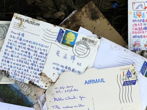 """欧新社发布的一张照片显示,马航MH17班机的残骸中,夹杂航空邮件,其中有中文书写的明信片。取自台湾""""中央社""""网站/欧新社供图"""