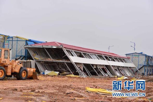 7月19日,在广东湛江徐闻县海安镇塘西村,一位村民抱着孩子站在被台风
