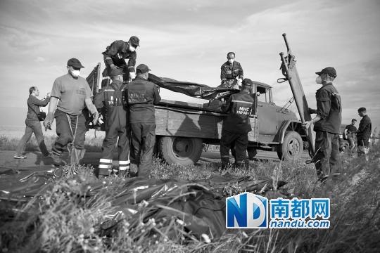 遇难者遗体被装在黑色袋子里运出坠机现场。