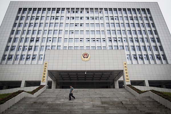 2014年6月24日,湖北省来凤县,一位男士走过县公安局。