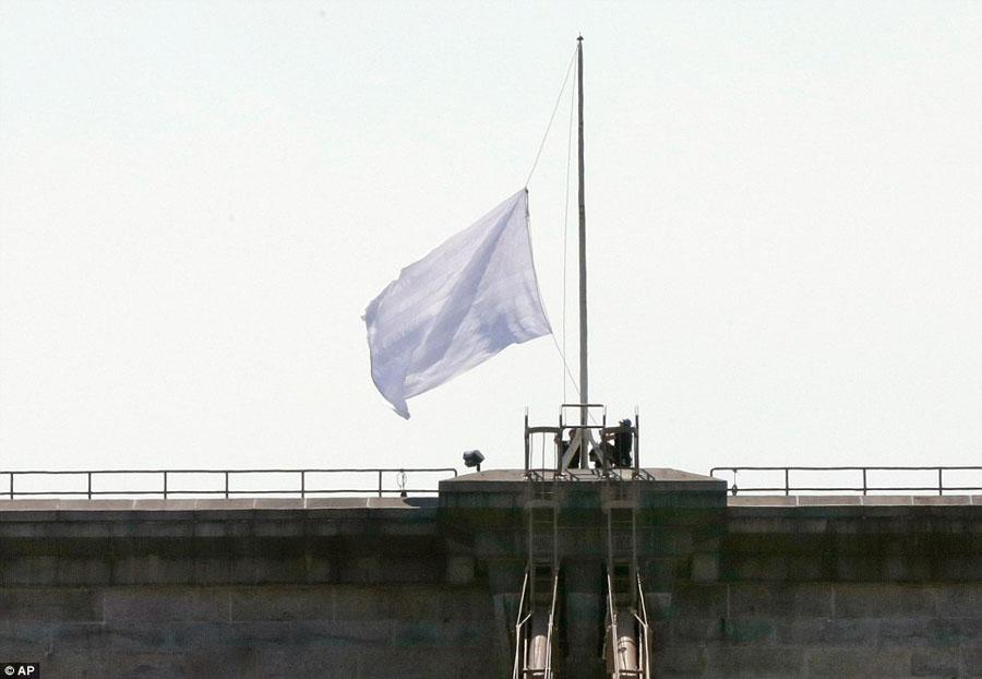 纽约布鲁克林大桥上升起似乎被漂白过的白旗,上面还有五角星和条纹印迹。