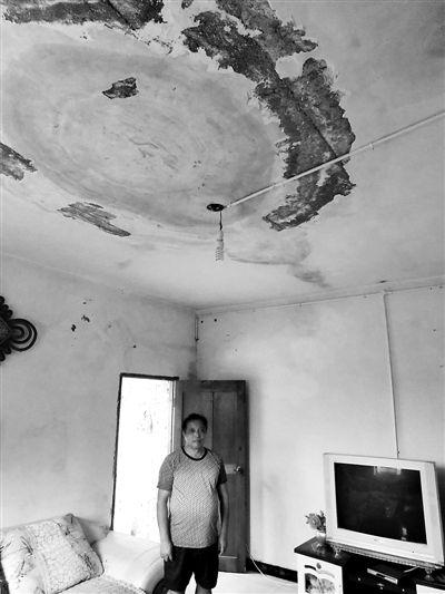 """王孝万家屋顶严重漏雨,当年作为""""接待家庭""""被配置的电视机仍摆在屋中 摄影/本报记者 薛雷"""