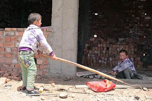 王鹏、王贺两兄弟在自家的建房工地上玩耍。