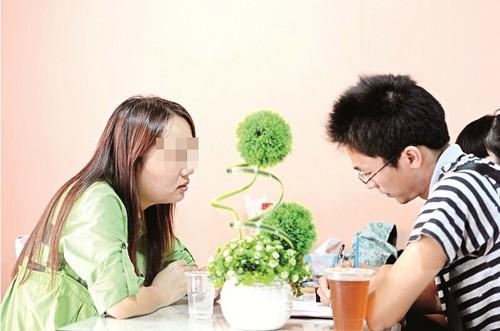 图为:刘敏(左)向本报记者讲述自己当代孕妈妈的经历